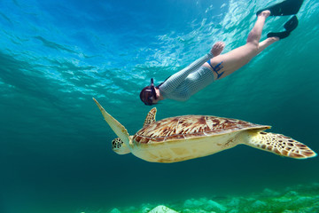 Fototapete - Young woman snorkeling with sea turtle