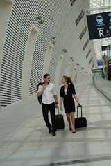 young business travelers man and woman walking in a public station