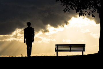 Silhouette of an anonymous man walking alone at sunset
