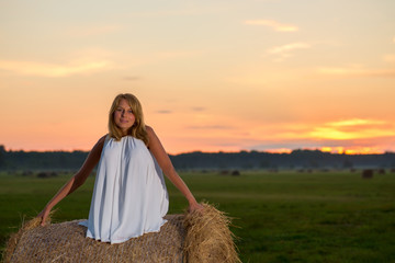 romantic woman in field with hay