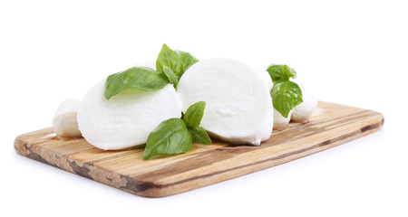 Tasty mozzarella with basil on wooden board isolated on white