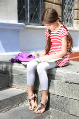 Cute girl with backpack on the steps outside