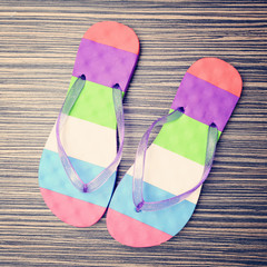 Bright flip-flop on wooden background.
