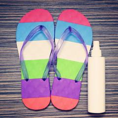 Flip flops and Bottle with suntan cream on wooden floor.
