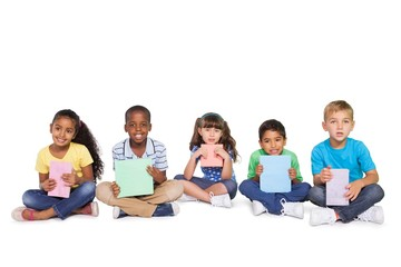 Cute children sitting and holding colour paper