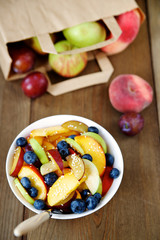 Fruit salad in a bowl on wooden background