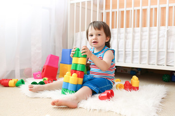 lovely baby boy playing toys at home