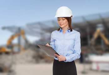 smiling businesswoman in helmet with clipboard
