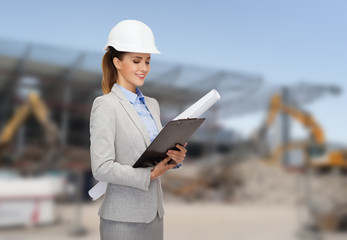 smiling architect in helmet with blueprint
