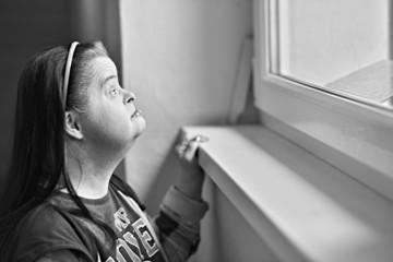 trisomique femme regarde par la fenêtre