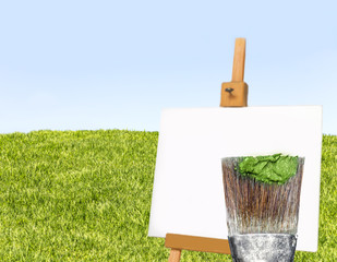 Creativity concept..Art paintbrush, paint,easel.Grass and sky