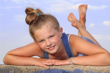 Wesoła dziewczynka leżąca na brzuchu na murku