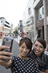 Women take a photograph on a mobile phone