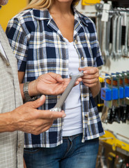 Midsection Of Woman With Father Holding Wrench In Shop