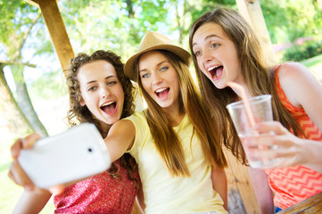 Girls taking selfie with smartphone in pub