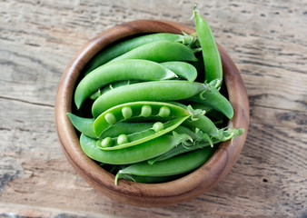 wooden bowl full  of green peas pods. Top view.