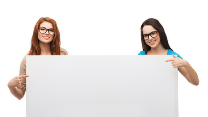 two smiling girls with eyeglasses and blank board