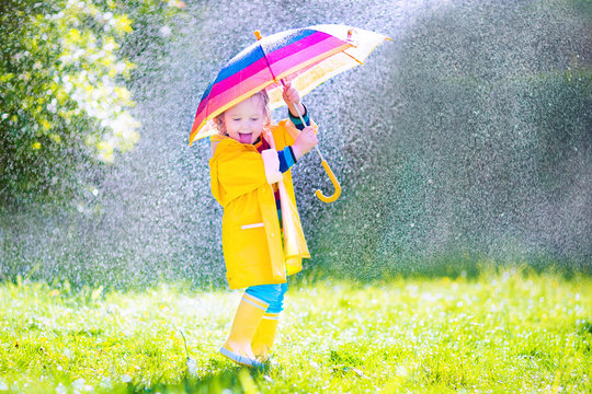 Funny little toddler with umbrella playing in the rain