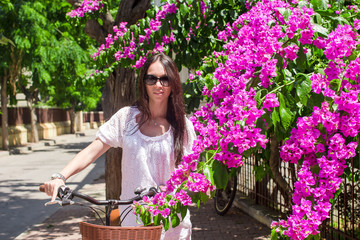 Young pretty woman on bicycle in summmer vacation