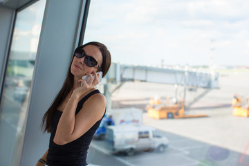 Young beautiful woman talking on the phone while waiting for