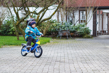 Little child of three years riding on bicycle in autumn or winte