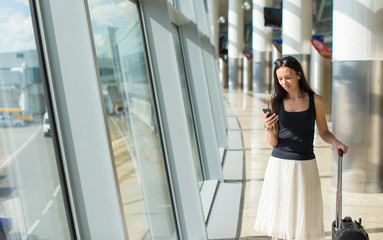 Young buzy woman with phone while waiting for flight
