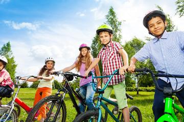 Row of happy children in bike colorful helmets