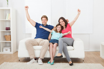 Cheerful Family With Arms Raised Sitting On Sofa