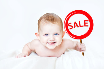"Smart little boy holding a sign ""SALE"" in the hands. In light ba"