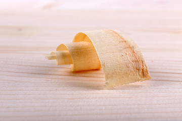 Wood shavings on wooden background closeup