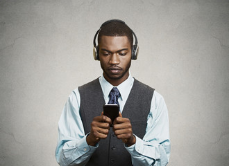 Phone addicted businessman with headphones, grey background