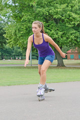 Woman is skating rollerblades in the park.