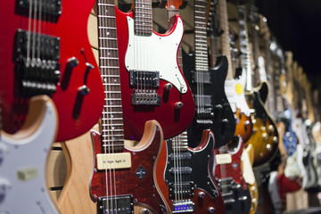 Fotorolgordijn Muziekwinkel Many electric guitars hanging on wall in the shop.