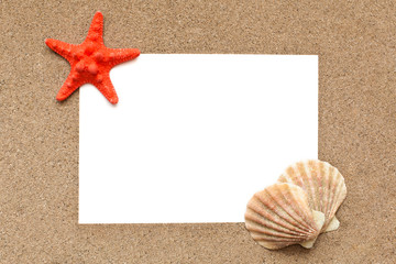 White sheet of paper with sea shells on sand