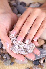 Female hand with stylish colorful nails on sea pebble