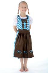 Kind im Dirndl zum Oktoberfest trägt Zöpfe