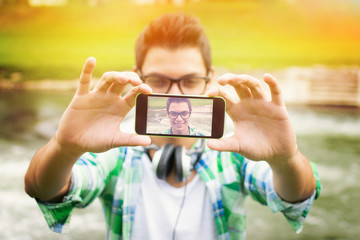 Young hipster man with headphones taking a selfie
