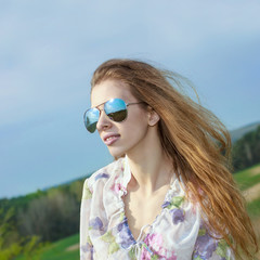 portrait of red long-haired beautiful girl in  sunglasses