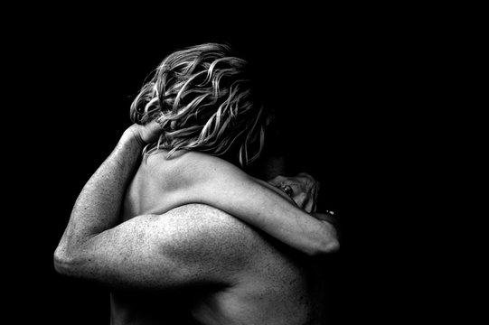 nude couple embrace dark