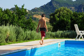 boy walks alone around the pool