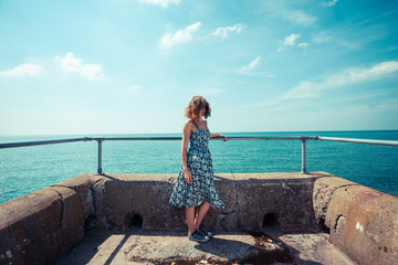 Young woman on a pier by the ocean