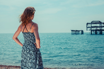 Young woman standing by the ocean with old pier