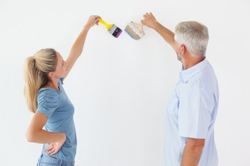 Happy couple painting wall with paintbrushes