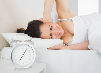 Sleepy woman covering ear with hand in bed