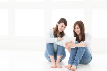 部屋でタブレットを見る二人の女性