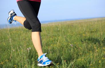 Runner athlete legs running on grass