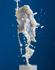 Splash white  liquid on a blue background.