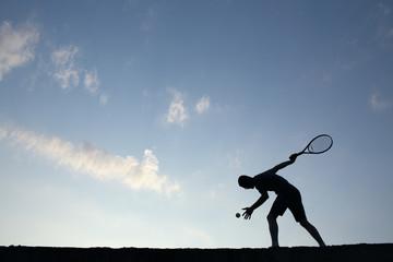 Silhouette of man playing tennis