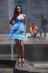 Fashionable woman in blue dress at the fountain