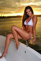 Seductive woman wearing white bikini posing on the luxury yacht.